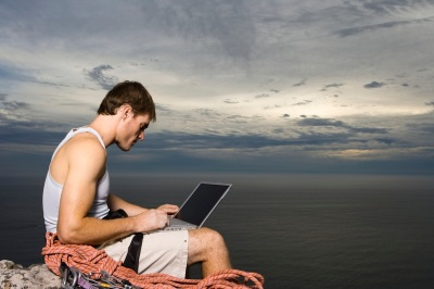 Man Using Laptop on a Cliff